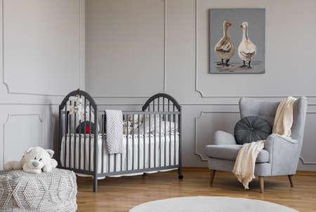 Giocattolo di peluche accanto al letto e poltrona all'interno della camera da letto del bambino grigio con poster. Foto reale