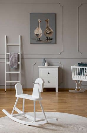 White rocking horse on rug in babys bedroom interior with poster above cabinet. Real photo