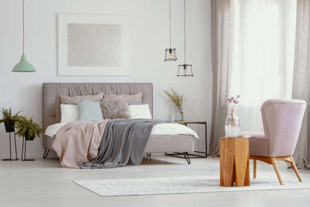 Flowers in glass vase on wooden coffee table next to stylish pastel pink armchair in elegant bedroom design with double bed with headboard and cozy bedding 免版税图像