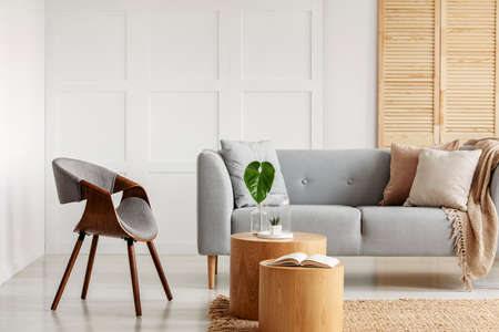 Real photo of a natural living room interior with an armchair, sofa and wooden accents