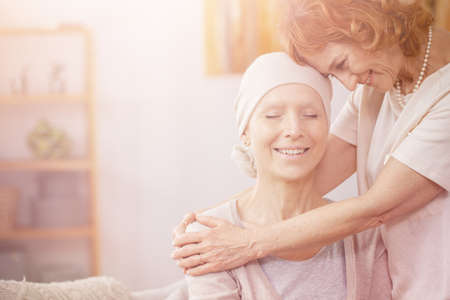 Bright photo of positive redhead woman hugging her sick partner who is suffering from lung cancer