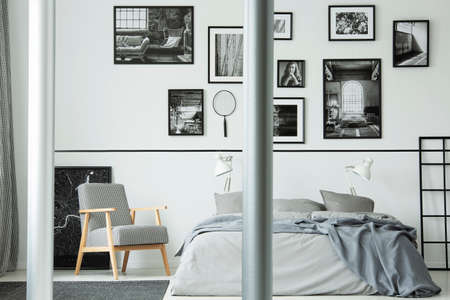 Wooden armchair next to bed in white bedroom interior with gallery of photos on the wall. Real photo