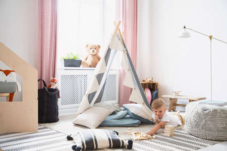 Boy having fun in a playroom interior with a tent, pillow and blocks