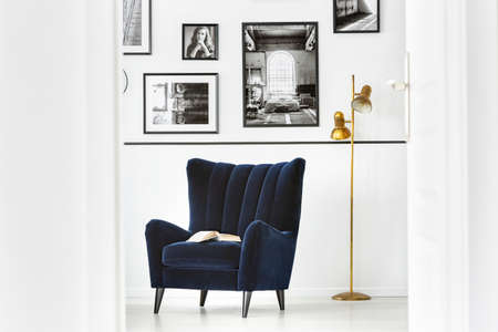Gold lamp next to dark armchair in white living room interior with gallery of posters. Real photo