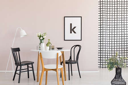 Black chairs at wooden table in modern dining room interior with poster and white lamp. Real photo