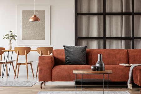 Open woon- en eetkamer interieur met lange tafel met stoel en bruin fluwelen bank