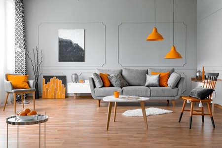 Geräumiges Wohnzimmer mit Couchtisch, stilvollen Stühlen und grauem bequemem Sofa Standard-Bild