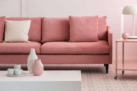 Pastelroze en witte vazen en koffiemokken op kleine tafel in roze woonkamerinterieur met comfortabele bank Stockfoto
