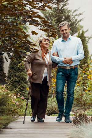Smiling man walking with happy elderly woman in the garden 스톡 콘텐츠