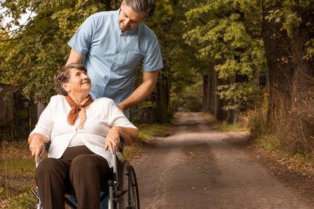 Male nurse supporting smiling senior woman in the wheelchair while walking in the forest