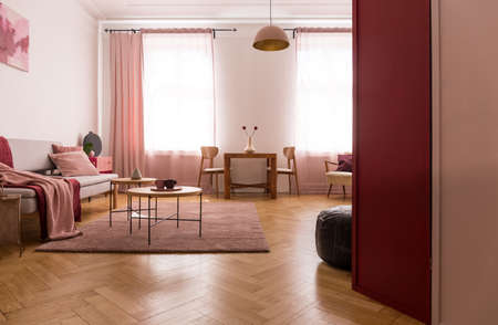 Wooden table on pink carpet in flat interior with blanket on sofa and drapes at window. Real photo