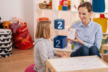 Lächelnder Therapeut, der während des Treffens mit einem autistischen Mädchen ein Bild des Rings zeigt