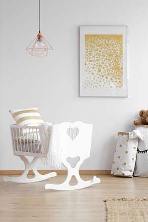 Lampada in rame sopra la culla bianca nell'interno della camera da letto del bambino semplice con poster giallo. Foto reale Archivio Fotografico