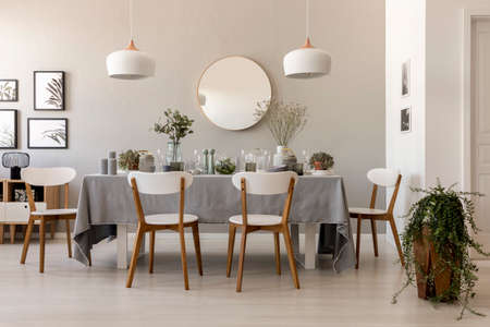 Dining table with fresh plants, glass vessels, candles and white chairs in real photo of living room interior with gallery, lamps and mirror on the wall Stock Photo