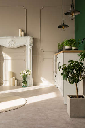 White fireplace portal with candles on grey wall of elegant kitchen