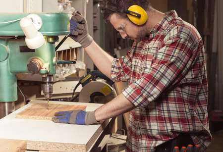 Technician with protective headphones using electric saw while cutting wooden desk Reklamní fotografie