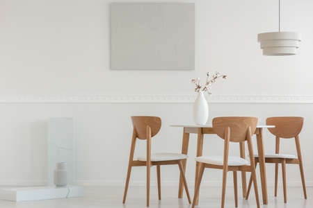 Spacious dining room interior with wooden chairs at desk and grey painting on the wall Stok Fotoğraf
