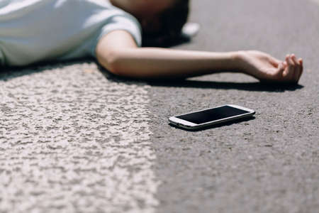 Smartphone on the pedestrian crossing after traffic accident with a person
