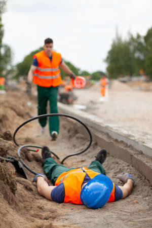Accident during road construction, injured worker lying on the ground