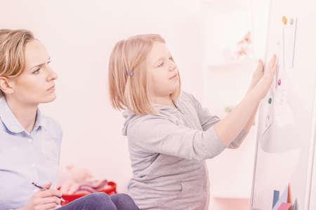 Ragazza con autismo che fa esercizi durante l'incontro con lo psicoterapeuta Archivio Fotografico