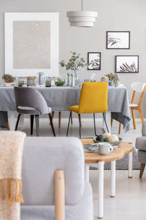 Grey and mustard chairs placed by the dining table with fresh plants, glasses and decor in real photo of small bright flat with posters