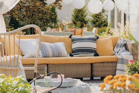 Real photo of a yellow, garden sofa with a table and lamps in the background. Close-up of plants