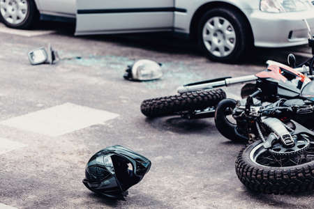 Helmet and motorcycle next to broken peaces of a car on the street after car crash