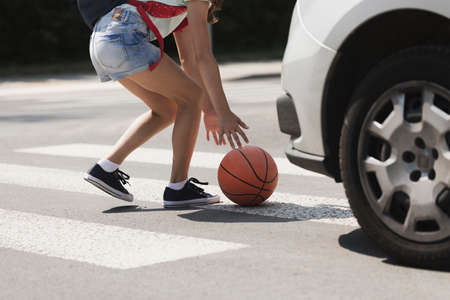 Careless kid holding a ball on the crosswalk in front of a car