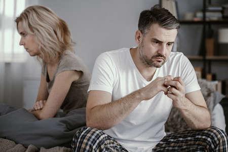 Mann im Pyjama, der im Bett sitzt und seinen Ehering abnimmt, nachdem seine Frau angekündigt hat, dass sie sich scheiden lassen möchte
