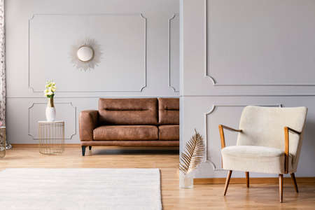 Real photo of a spacious living room interior with a white rug, armchair and leather sofa