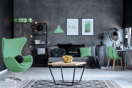 Zielony fotel obok drewnianego stołu w ciemnym salonie wnętrza z plakatami nad kanapą. Prawdziwe zdjęcie Zdjęcie Seryjne
