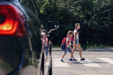 Kinderen naast een auto lopen door zebrapad naar de school