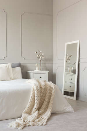 Mirror in white frame on grey wall of stylish scandinavian bedroom interior with king size bed with cozy blanket