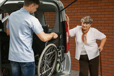 Caregiver holding wheelchair in the car for disabled elderly woman with walking stick Foto de archivo - 121161616