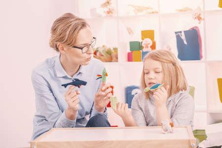 Madre sosteniendo juguetes mientras juega con su hija concentrada con síndrome de Asperger