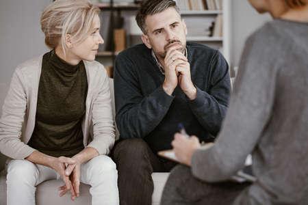 Esposa apoyando a su marido en terapia con el hombre escuchando con curiosidad al consejero Foto de archivo