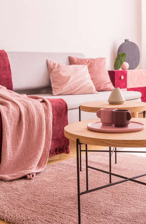 Cups on wooden table next to sofa with pink pillows in living room interior with carpet. Real photo