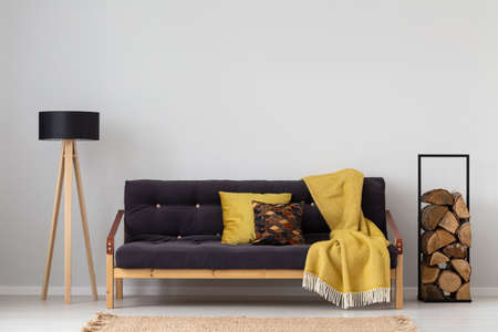 Yellow blanket on settee between lamp and logs of wood in grey apartment interior. Real photo