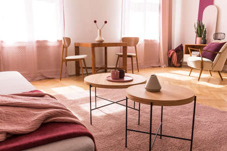 Round wooden tables on pink carpet in apartment interior with couch and armchair. Real photo