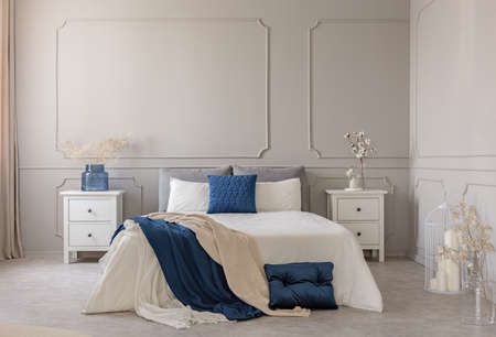 Copy space on empty grey wall of scandinavian bedroom interior with blue, white and grey design Stok Fotoğraf - 121161630