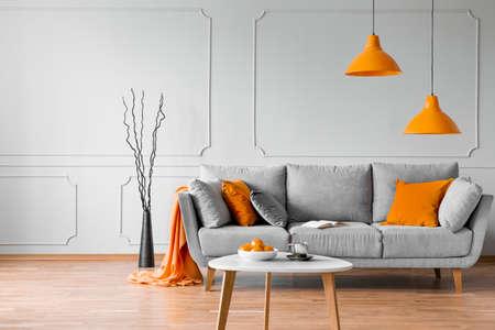 Echtes Foto eines einfachen Wohnzimmerinterieurs mit orangefarbenen Lampen, Kissen und grauem Sofa