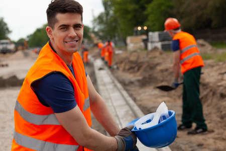 Hübscher junger Straßenbauarbeiter in orangefarbener Sicherheitsweste