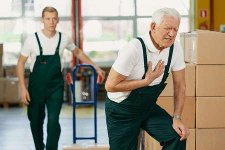 Älterer Lagerist mit Herzinfarkt bei der Arbeit, junger Kollege rennt, um ihm zu helfen Standard-Bild