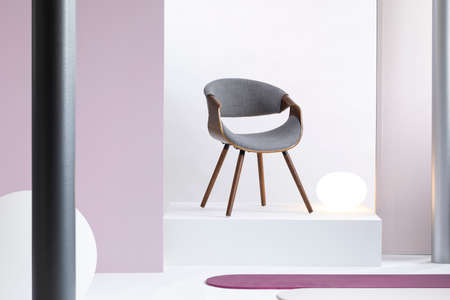 Real photo of a simple, white and purple room interior with a gray chair on a podium