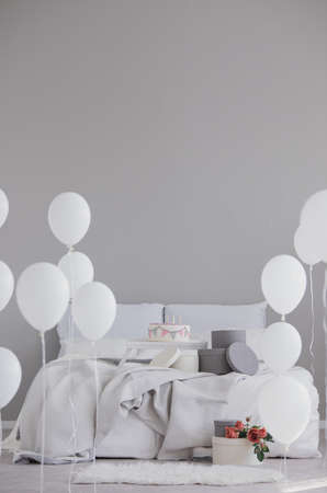 Elegant bedroom with king size bed with grey bedding, birthday cake and white balloons, real photo with copy space on empty wall Banco de Imagens