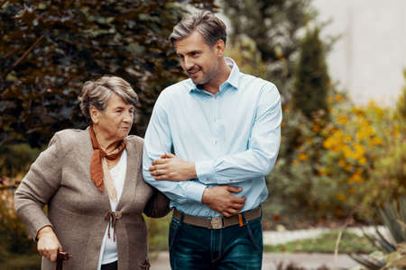 Smiling man supporting senior woman while walking in the garden