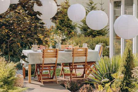 Foto real de lámparas redondas sobre una mesa con sillas de madera en un jardín.