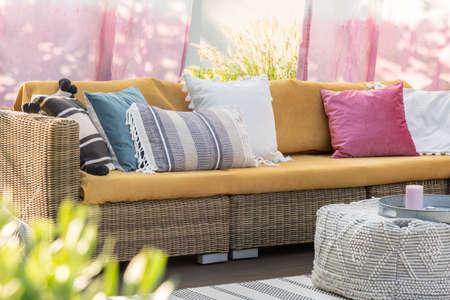 Vraie photo d'oreillers colorés sur un canapé en rotin sur la terrasse