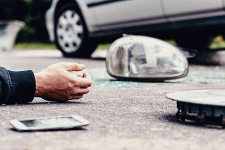Human's hand on the ground next to broke car mirror and mobile phone after a crash 版權商用圖片
