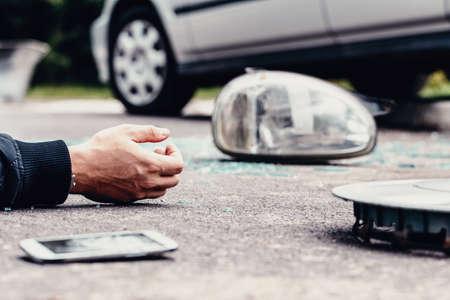 Menselijke hand op de grond naast kapotte autospiegel en mobiele telefoon na een crash